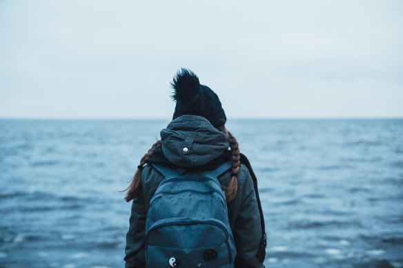 back view of a person carrying a backpack looking into the ocean